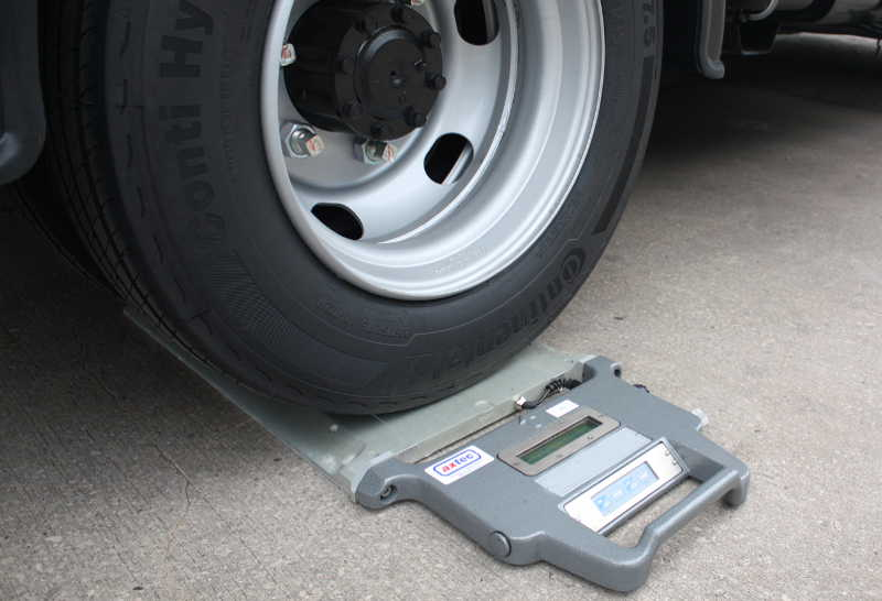 Image of a portable system, underneath a wheel of a vehicle
