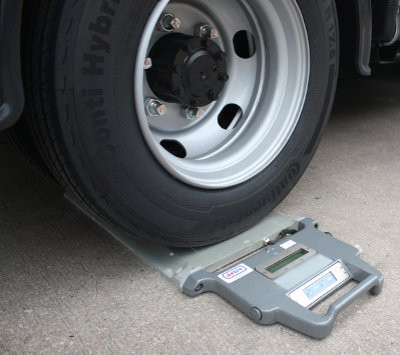 Axtec Portable Weighpad with a wheel sitting atop